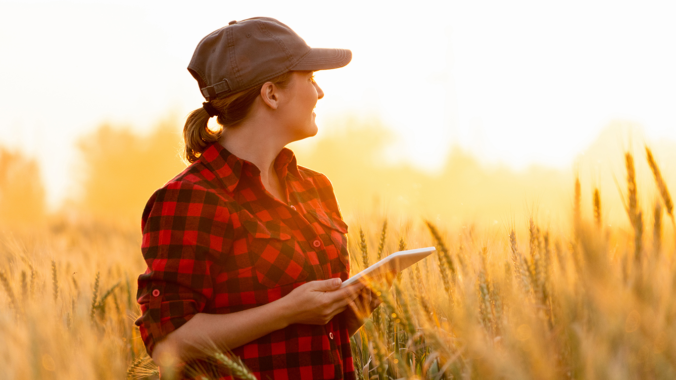 Woman standing in wheat field with tablet